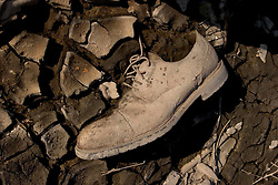 30 Sept, 2005.  New Orleans, Louisiana.  Lower 9th ward. Hurricane Katrina aftermath.<br /> The remnants of the lives of ordinary folks, now covered in mud as the flood waters remain. A man's shoe lies stuck in the mud.<br /> Photo; ©Charlie Varley/varleypix.com