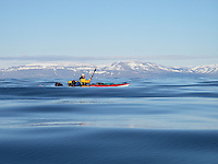 The kayak is almost hidden by the waves on the Isfjord on Spitzbergen