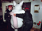 Policed arrest a protestor dressed in a mouse costume outside a meeting of genetic scientists in Toronto, Ont. (1994)
