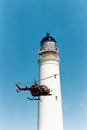 A supply helicopter lands next to the lighthouse on the uninhabited island of Hyskeir, eight miles from Rum in the Inner Hebrides on Scotland's west coast.  The helicopter was delivering supplies to workmen who were converting the lighthouse from manned to automatic. The lighthouse was operated by the Northern Lighthouse Board and was one of the last in Scotland to be automated.