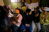 Marquis B-eazi Johnson,bottom left, his girlfriend Cynphaney Johnson, center in yellow, and friends from the Lower Bottoms pass a bottle around prior to a video shoot and hotel party.