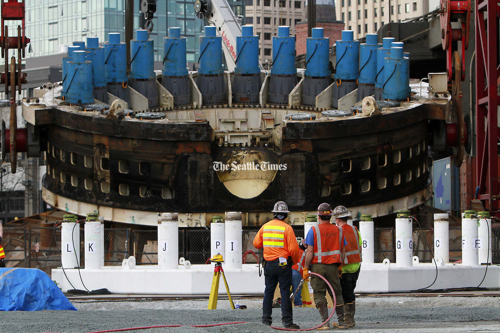 After being trapped underground and broken, a cutting head assembly is finally brought to the surface for repairs, temporarily stopping some workers in their tracks.<br /> <br /> Ken Lambert / The Seattle Times