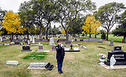 First Sgt. Dean Weiss performs taps during a military flag folding ceremony on Monday morning in the Mitchell cemetery. (Matt Gade / Republic)