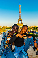 Young African women posing for a photo with the EIffel Tower in background at Trocadero, Paris, France.