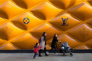 Asian shoppers walk beneath the temporary construction hoarding facade of luxury accessories brand, Louis Vuitton on New Bond Street, on 19th February 2019, in London, England.