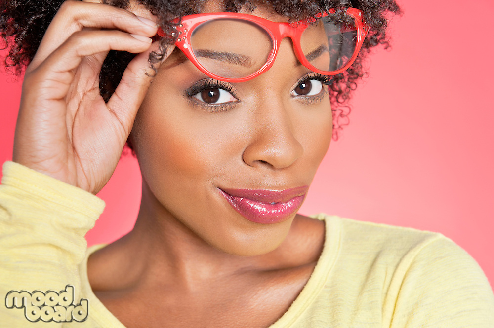 Portrait of an African American woman holding retro glasses over colored background