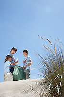 Three boys (7-12) collecting rubbish on sand dune view from below