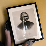 """October 13, 2015 - New York, NY : A curated reinstallation of art and antiques is currently underway in the Mayor's House, Gracie Mansion, as it is being prepped for reopening. Here, Jonathan Elliott, the consulting registrar for the Gracie Mansion Conservancy, hangs """"Frederick Douglass (1818 - 1895), ca. 1873,"""" a piece from the Museum of the City of New York, on Tuesday morning. CREDIT: Karsten Moran for The New York TImes"""