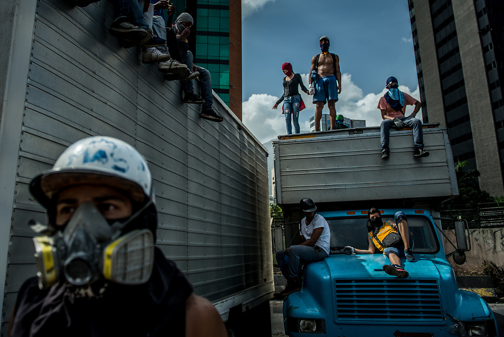 "CARACAS, VENEZUELA - MAY 27, 2017:  Anti-government protesters of ""The Resistance"" use two industrial sized trucks that they highjacked     as road blocks to shut down the main highway that runs through Caracas. The streets of Caracas and other cities across Venezuela have been filled with tens of thousands of demonstrators for nearly 100 days of massive protests, held since April 1st. Protesters are enraged at the government for becoming an increasingly repressive, authoritarian regime that has delayed elections, used armed government loyalist to threaten dissidents, called for the Constitution to be re-written to favor them, jailed and tortured protesters and members of the political opposition, and whose corruption and failed economic policy has caused the current economic crisis that has led to widespread food and medicine shortages across the country.  Independent local media report nearly 100 people have been killed during protests and protest-related riots and looting.  The government currently only officially reports 75 deaths.  Over 2,000 people have been injured, and over 3,000 protesters have been detained by authorities.  PHOTO: Meridith Kohut"