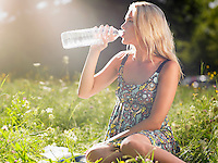 Young woman sitting in meadow drinking water from bottle