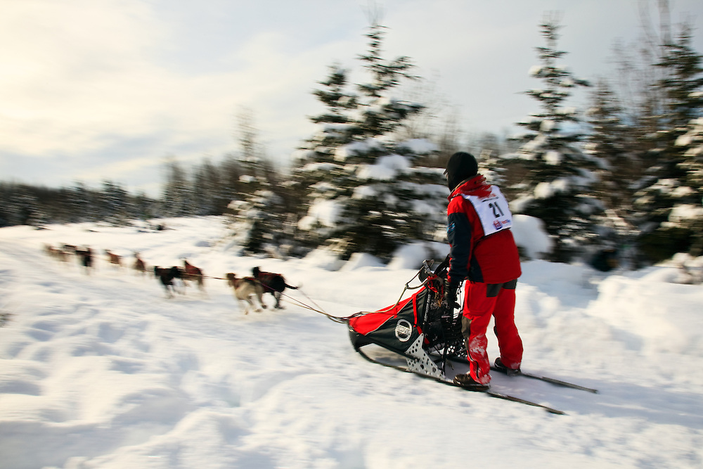 Musher Ken Chezik and sled dogs in the Fur Rendezvous World Sled Dog Championships on the Campbell Creek Trail in Anchorage, Alaska. Southcentral. Afternoon.