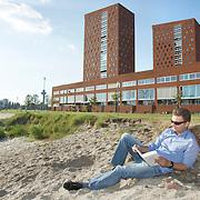 """Nederland Rotterdam 30-05-2009 20090530 Foto: David Rozing ..Nieuwbouw woningen in probleemwijk Katendrecht, man leest boek aan het strandje terwijl een kind in het zand speelt, met op de achtergrond de nieuwbouw woningen en euromast. Stedelijke vernieuwing, relaxen, relaxed, ontspanning, vrije tijd, van het zonnetje genieten, zomers,  zomerse dag, zomers, zonnig, zonnige, zon, lekker weer, genieten, ontspanning, rust, huisje boompje beestje, ruime moderne wijk, vrij uitzicht, strand New houses / appartments in (former) deprived area / projects """"Katendrecht """" This area is on a list with projects which need help of the government because of degradation in the area etc.city, beach,project, suburb, suburbian, problem. Neighboorhood, neighboorhoods, district, city, problems,  daily life Holland, The Netherlands, dutch, Pays Bas, Europe ..Foto: David Rozing"""
