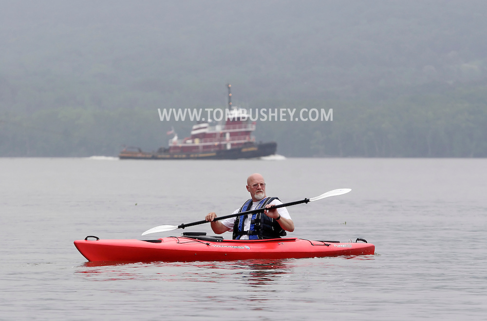 New Windsor, New York - A man paddles his kayak on the Hudson River as a tug boat heads south in the background at the Paddlefest event sponsored by the Mid-Hudson Chapter of the Adirondack Mountain Club at Kowawese Unique Area at Plum Point on  June 13, 2010.