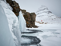 Kirkjufellsfoss waterfall in winter. Mount Kirkjufell in background. Snæfellsnes Peninsula, West Iceland.