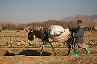 """Towr Nasr, Afghanistan, 14-01-07, Dagelijks leven op het platteland van Uruzgan...Boy in green boots in the Afghan countryside near Deh Rawod..The Dutch army has been in the southern Afghan province Uruzgan since mid 2006. The initial idea was to focus on reconstruction of the province, and win the """"hearts and minds"""" of the Afghan people. The province turned out to be a hotbed for Taliban support so the mission that started so peacefully, turned into a fighting mission. Political tension on how to continue this mission has been rising in the Netherlands since the first bodybags started coming home."""