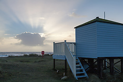 © Licensed to London News Pictures. 06/01/2014. Mudeford Spit, Christchurch, Dorset, UK. Sunrise near the beach huts on Mudeford Spit near Christchurch in Dorset, UK. The beach huts sell for an average of around £140,000. Dorset is expected to be one of the worst affect areas, with more heavy rain and flooding forecast. Photo credit : Rob Arnold/LNP
