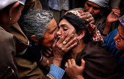 BADGAM, INDIA, MARCH 10, 2004:A Kashmiri woman comforts her relative as they mourn the death of five people who were killed along with  48 who were injured, when a grenade exploded in the hands of a man who was seeking to extort money from a family in Badgam district of Kashmir, March 10, 2004.   Locals said the man was a former militant who was extorting money from villagers and thousands came out to mourn the deaths. Tens of thousands of people have died in Kashmir since the eruption of anti-Indian revolt in the region in 1989. Separatists put the toll at between 80,000 and 100,000.