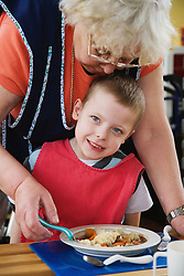 Boy with physical and learning difficulties being served a meal at lunchtime,