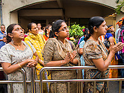 05 OCTOBER 2014 - GEORGE TOWN, PENANG, MALAYSIA: Hindu women pray during a procession honoring Durga in George Town during the Navratri procession. Navratri is a festival dedicated to the worship of the Hindu deity Durga, the most popular incarnation of Devi and one of the main forms of the Goddess Shakti in the Hindu pantheon. The word Navaratri means 'nine nights' in Sanskrit, nava meaning nine and ratri meaning nights. During these nine nights and ten days, nine forms of Shakti/Devi are worshiped.   PHOTO BY JACK KURTZ