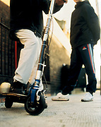 Two teenage chavs standing on the street, one on a motorised scooter, UK 2000's