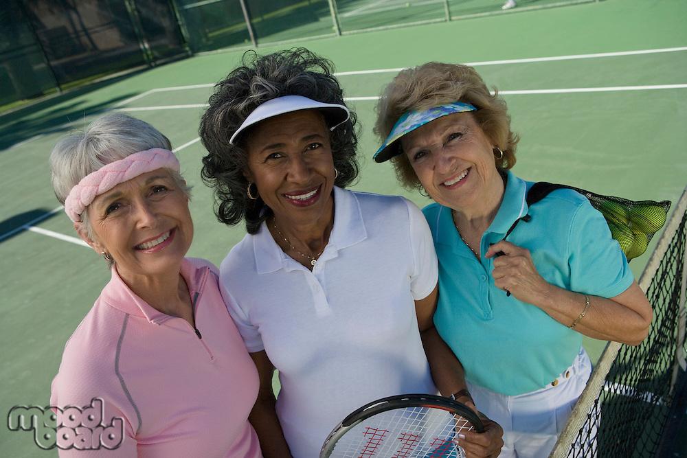 Three women on tennis court, portrait