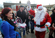 LEVITTOWN, PA -  DECEMBER 21:  Santa Claus visits Hannah Pizzullo as she rests in her carrier with her mother Vicki Pizzullo (L) and father Justin Pizzullo (C) visitors sing Christmas carols at the Pizzullo home December 21, 2013 in Levittown, Pennsylvania. Hannah was born with Krabbe, a genetic disorder that affects both the central and peripheral nervous systems. The family is fighting to make newborn screening for the disorder a state law. (Photo by William Thomas Cain/Cain Images)