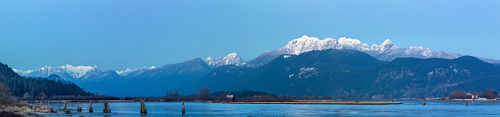 View of the Golden Ears, Raven Peak and Osprey Mountain (left) and the Pitt River from the Traboulay Poco Trail in Port Coquitlam, British Columbia, Canada.