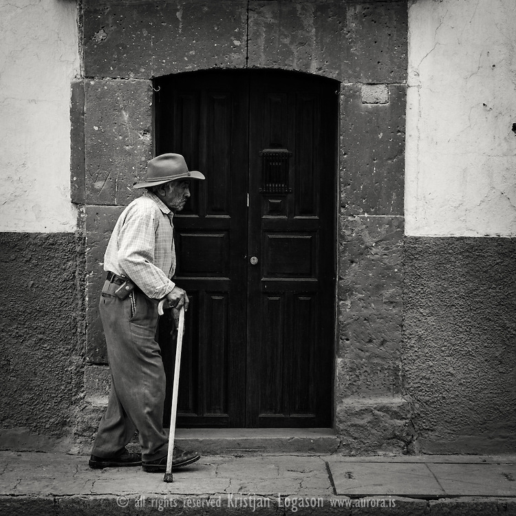 Old man with a walking stick walking in the street of San Miguel de allende