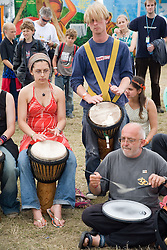 Group of people watching men and women playing tomtoms at the WOMAD (World of Music; Arts and Dance) Festival in reading; 2005,