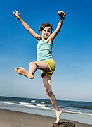 Girl plafully jumping from a beach pier, Stone Harbor, New Jersey, USA