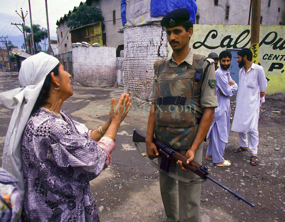 July 1997. Srinagar, Kashmir, India..A Kashmiri mother pleads with an Indian soldier for the release of her son from an interrogation center (in background). Her son, a suspected militant was severely beaten and abducted by 'Renegades' from the family business. The 'Renegades' are a quasi police force, loosely linked to the police and responsible for the abduction, torture and disappearance of many 'suspected' or accused rebels. The 'Renegades' demand hefty ransom for the safe return of loved ones. .Photo; Charlie Varley