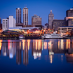 Picture of Peoria Illinois skyline at night with downtown city buildings reflection on the Illinois River and the Spirit of Peoria paddlesheel riverboat.