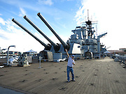 Wayne Koch points in the direction of her huge guns as the USS Iowa battleship sits docked as a museum and tourist attraction in the San Pedro Harbor on November 30, 2013 in Los Angeles, California. ©Paul Anthony Spinelli