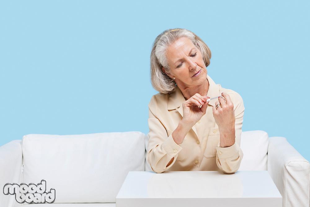Senior woman filing nails at home