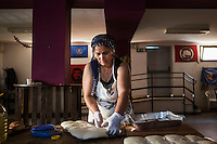 "ROME, ITALY - 3 JULY 2016: Gipsy Queen member Micescu Mieila (49) shapes dough for pitas for their food stand at the iFest, an alternative music festival, here in the Astra 19 social center in Rome, Italy, on July 3rd 2016.<br /> <br /> The Gipsy Queens are a travelling catering business founded by Roma women in Rome.<br /> <br /> In 2015 Arci Solidarietà, an independent association for the promotion of social development, launched the ""Tavolo delle donne rom"" (Round table of Roma women) to both incentivise the process of integration of Roma in the city of Rome and to strengthen the Roma women's self-esteem in the context of a culture tied to patriarchal models. The ""Gipsy Queens"" project was founded by ten Roma women in July 2015 after an event organised together with Arci Solidarietà in the Candoni Roma camp in the Magliana, a neighbourhood in the South-West periphery of Rome, during which people were invited to dance and eat Roma cuisine. The goal of the Gipsy Queen travelling catering business is to support equal opportunities and female entrepreneurship among Roma women, who are often relegated to the roles of wives and mothers."
