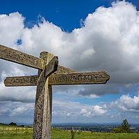 View across farmland from the top of the Sussex Downs near Storrington with wooden sign post