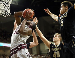 Texas A&M's Jalen Jones (12) goes up for a shot against Vanderbilt's Luke Kornet (3), Josh Henderson (40) and Matthew Fisher-Davis (5) during the first half of an NCAA college basketball game, Saturday, March 5, 2016, in College Station, Texas. Texas A&M won 76-67. (AP Photo/Sam Craft)