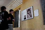 "Two young visitors at the Tuol Sleng Genocide Museum in Phnom Penh, Cambodia are transfixed by the story of Mong Sam Oeun, presently a power plant worker, posted on a wall that offers an historical reminder of past war atrocities perpetrated by the Pol Pot regime from 1975-1979. Tourists and Cambodian residents alike visit this dormitory like wing that was used to keep dozens of supine prisoners shackled together while they awaited an inevitable trip to Choun Eak, otherwise known as ""The Killing Fields""."