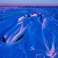 Snow drifts in Wapusk National Park illuminated by soft light at sunset.