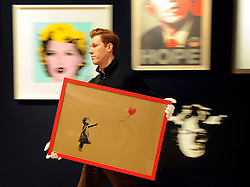 © Licensed to London News Pictures. 23/03/2012. London, UK. Bonham's staff member carries a Banksy original, Girl and Balloon, 2009 (estimate £15,000  25,000), the artist has painted his iconic image directly onto the cardboard backing of an Ikea frame. Next to the Swedish companys label on the reverse he has added the words high quality. A photocall of Bonham's Urban Art Sale including Seventeen art works by the celebrated graffiti artist, Banksy, which are to be sold at Bonhams, London, ahead of the Urban Art Sale, which takes place on 29 March 2012. . Photo credit : Stephen SImpson/LNP