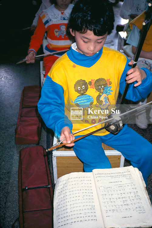 Boy plays Erhu, traditional Chinese musical instrument, at Children's Palace (for after school programs), Shanghai, China