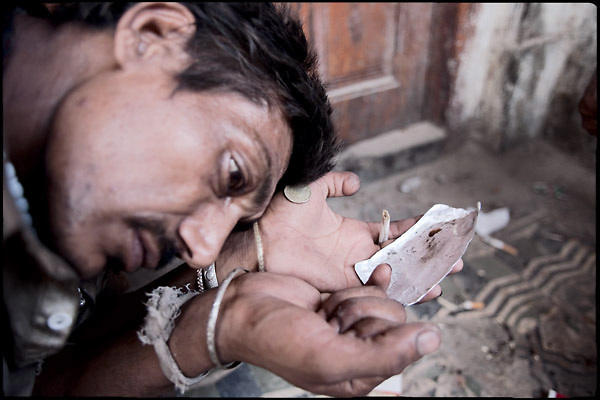 """Khalid, 27 years old, homeless and heroin addict, is having few minutes of rest after consumption of his dose. He usually smokes the drug putting a coin in the mouth, just to let the hot smoke hits it, without burning the palate. Many druggies use the same method to allow the smoke spreads in the mouth, once hit the change. Rawalpindi, Pakistan, on friday, August 29 2008.....""""Pakistan is one of the countries hardest hits by the narcotics abuse into the world, during the last years it is facing a dramatic crisis as it regards the heroin consumption. The Unodc (United Nations Office on Drugs and Crime) has reported a conspicuous decline in heroin production in Southeast Asia, while damage to a big expansion in Southwest Asia. Pakistan falls under the Golden Crescent, which is one of the two major illicit opium producing centres in Asia, situated in the mountain area at the borderline between Iran, Afghanistan and Pakistan itself. .During the last 20 years drug trafficking is flourishing in the Country. It is the key transit point for Afghan drugs, including heroin, opium, morphine, and hashish, bound for Western countries, the Arab states of the Persian Gulf and Africa..Hashish and heroin seem to be the preferred drugs prevalence among males in the age bracket of 15-45 years, women comprise only 3%. More then 5% of whole country's population (constituted by around 170 milion individuals),  are regular heroin users, this abuse is conspicuous as more of an urban phenomenon. The substance is usually smoked or the smoke is inhaled, while small number of injection cases have begun to emerge in some few areas..Statistics say, drug addicts have six years of education. Heroin has been identified as the drug predominantly responsible for creating unrest in the society."""""""