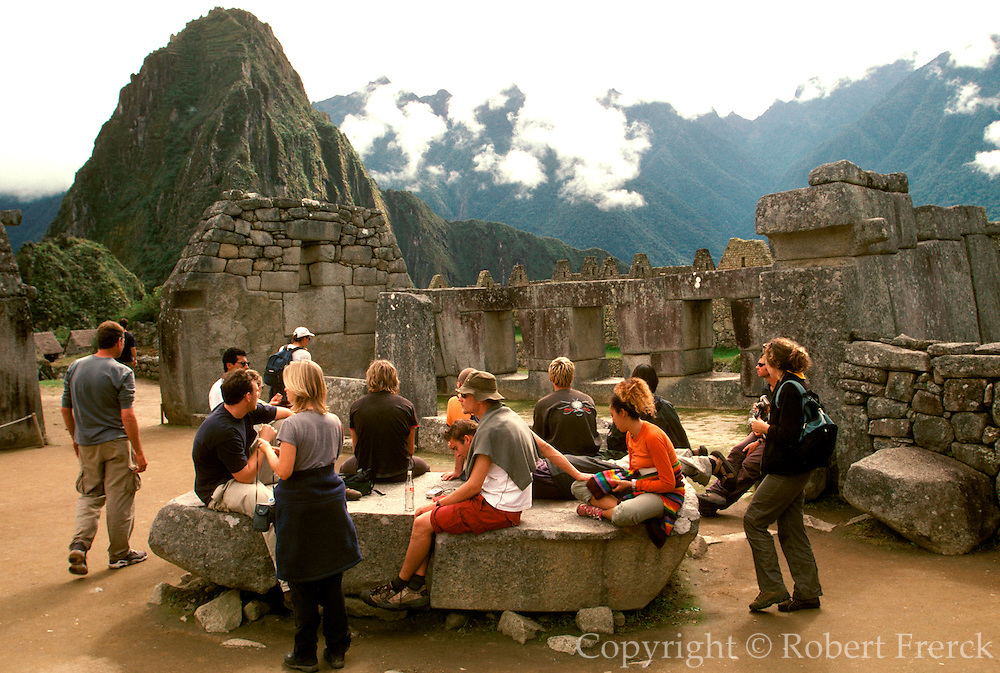 PERU, HIGHLANDS, PREHISPANIC, INCA Machu Picchu; the ancient city with visitors  viewing the temples in the Sacred Precinct