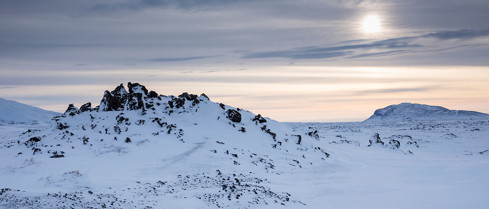 Wintry sun and clouds above snow-covered mountains and landscape of lava fields in South Iceland