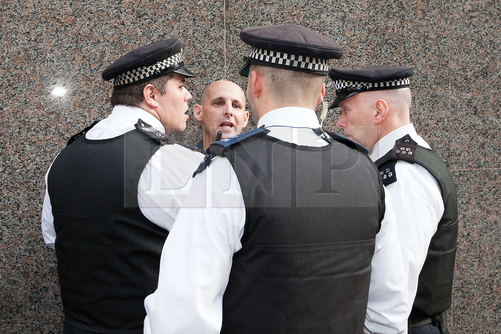 © Licensed to London News Pictures. 11/09/2011. London, UK. Police scuffle with and detain an EDL protester trying to confront Muslims Against Crusaders protesters on Edgware Road as MAC are lead back to the Regents Park Mosque following their demonstration Radical Islamist group, Muslims Against Crusades, hold a protest outside the US Embassy in Grosvenor Square, London, on the 10th anniversary of the September 11th terrorist attacks on America. A counter-protest was held at the same time by the English Defence League. Photo credit : Joel Goodman/LNP
