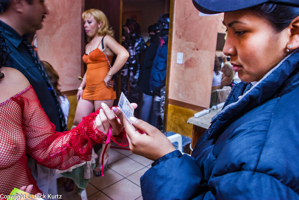 05 FEBRUARY 2005 - NOGALES, SONORA, MEXICO: Police officers in Nogales, Sonora, check the ID cards of entertainers in an adult entertainment business during a sweep to crackdown on drug dealers and gang members.  PHOTO BY JACK KURTZ