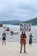 Climate change activists from Extinction Rebellion standing in solidarity with the world wide protest, Black Lives Matter following the death of George Floyd in the USA in their weekly protest called No Going Back which is usually linked to climate change and has now grown to become a national event, on Sunday at 10.00am on the 7th June 2020 in St Ives, United Kingdom. Black Lives Matter is an international human rights movement, originating from within the African-American community which campaigns against violence and systemic racism towards black people. Around 40 members of the St Ives community decided to protest by standing for an hour holding placards with slogans such as 'Black Lives Matter' and 'I can't breathe'. They walked through the town to the beach and harbour.