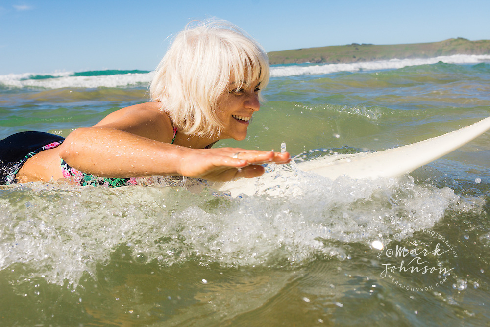 Woman surfer paddling her surfboard in the surf, Sandy Beach, Coffs Harbor, NSW, Australia