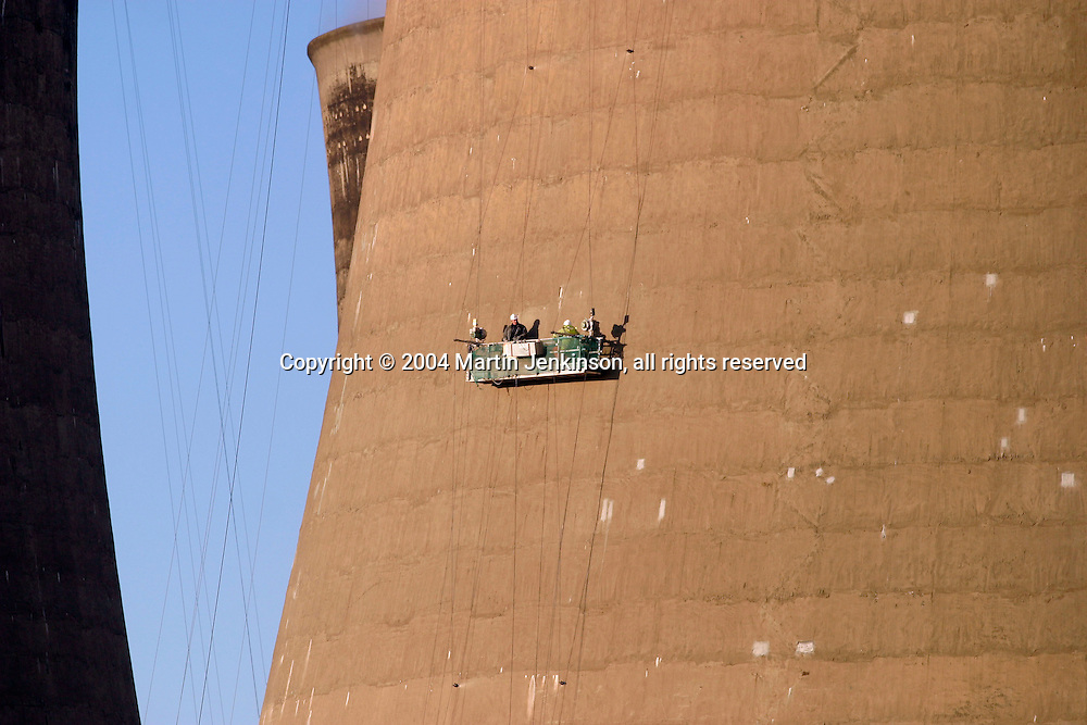 Workmen using a cradle to access the outside of a cooling tower at Eggborough coal fired power station.