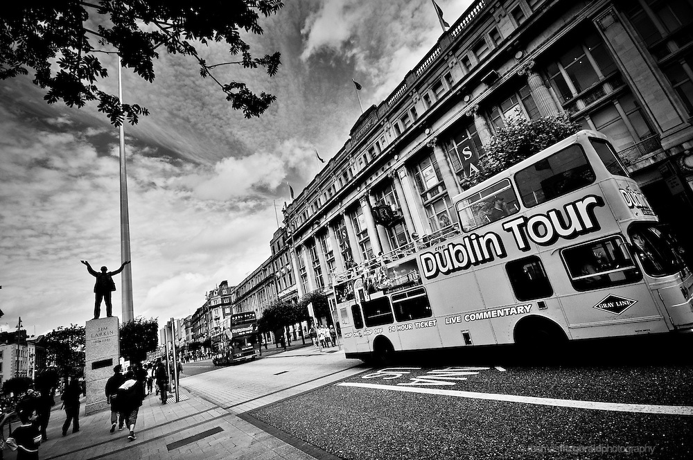 Dublin City, Ireland: A Dublin Tour Bus waits outside the famous Cleary's Department Store on O'Connell Street, while in the background tourists gather around the statue of Jim Larkin and the Iconic Spire